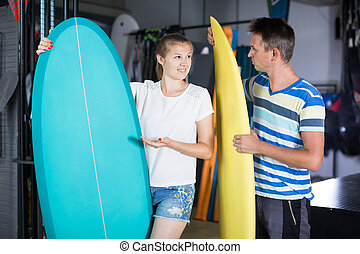 Cheerful couple is choosing colorful boards