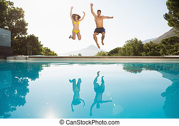 Cheerful couple jumping - Full length of a cheerful young...