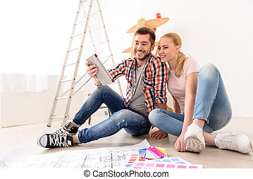 Cheerful couple looking at construction house plan - So many...