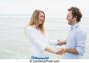 Cheerful couple looking at each other at beach