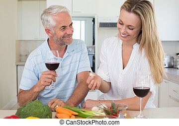 Cheerful couple making dinner together and drinking red wine