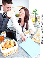 Cheerful couple ob businesspeople having breakfast in the kitchen at home