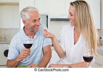 Cheerful couple preparing dinner together and drinking red wine