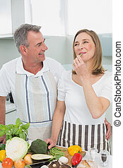Cheerful couple preparing food together in kitchen