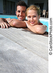 Cheerful couple relaxing in swimming pool
