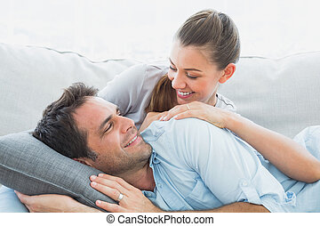 Cheerful couple relaxing on their sofa smiling at each other