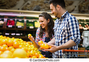Cheerful couple shopping for organic fruit
