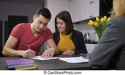 Cheerful couple signing contract with estate agent