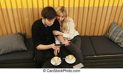 Cheerful couple sitting at coffee shop and websurfing on tablet