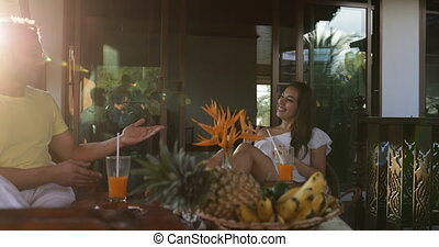 Cheerful Couple Sitting At Table On Terrace Talking, Happy Man And Woman Cheering With Juice Glasses Smiling
