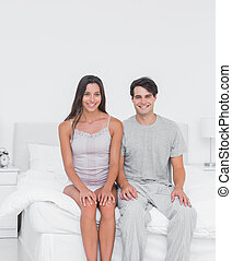 Cheerful couple sitting in bed