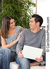 Cheerful couple sitting on a sofa