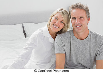 Cheerful couple sitting on bed