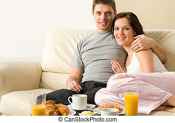 Cheerful couple sitting on couch before breakfast