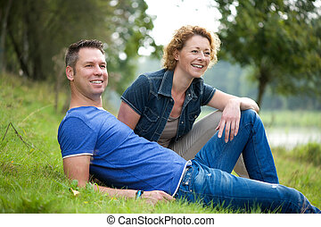 Cheerful couple sitting on grass outdoors