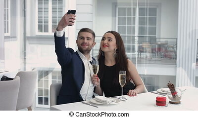cheerful couple taking a humorous selfie with a smartphone at the restaurant