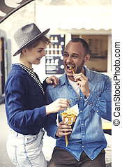 Cheerful couple trying take out food