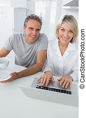 Cheerful couple using laptop in the morning looking at camera