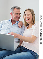 Cheerful couple using laptop on sofa
