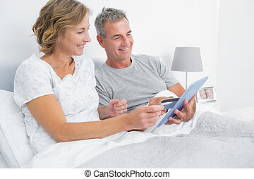 Cheerful couple using their tablet