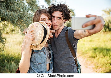 Cheerful couple w hiking in the forest and making selfie