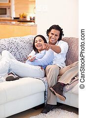 Cheerful couple watching television together