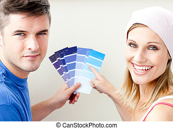 Cheerful couple with color samples for painting a room in...