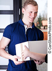 Cheerful courier giving delivery