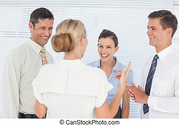 Cheerful coworkers having a break together in staff room