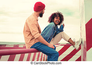 Cheerful curly girl sitting with her boyfriend and smiling while drinking blue lemonade