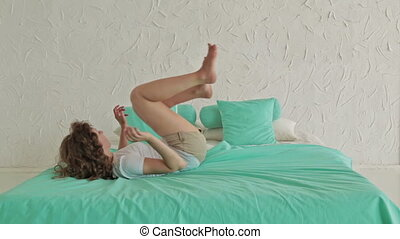 Cheerful curly woman jumping on bed