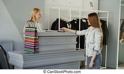 Cheerful customer is paying with credit card for purchased clothes while standing at cashier's desk. Shop assistant is accepting transaction and giving her paper bag.