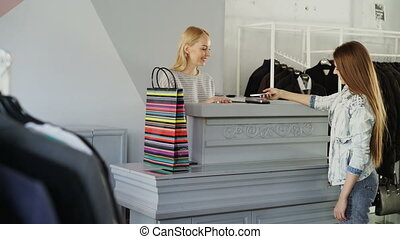 Cheerful customer standing at cashier's desk, chatting with saleswoman and paying for purchases with smartphone. Shop assistant handing her shopping paper.