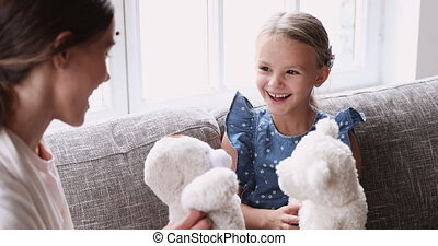 Cheerful cute child girl playing stuffed toys with parent mom