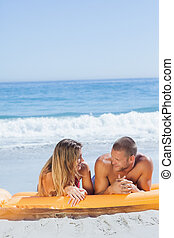 Cheerful cute couple in swimsuit relaxing together
