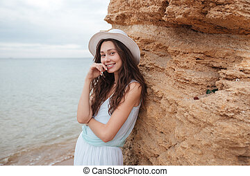 Cheerful cute girl standing near the rock on the beach