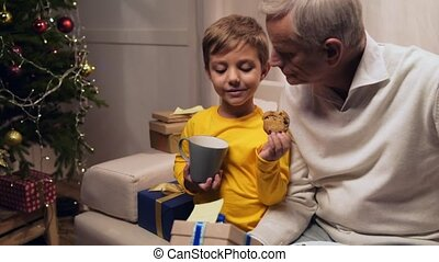 Cheerful cute little bot helping his grandfather to prepare Christmas presents