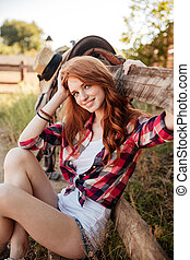 Cheerful cute young woman cowgirl siting on farm - Portrait...