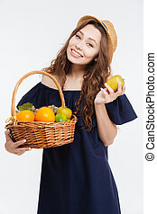 Cheerful cute young woman in hat holding basket with fruits