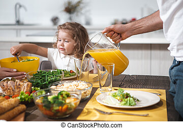 Cheerful dad serving healthy drink for his daughter