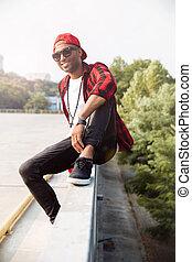 Cheerful dark skinned man wearing sunglasses against nature background