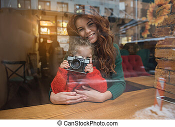 Cheerful daughter using photo camera near mother