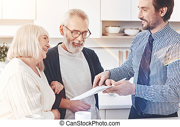 Cheerful delighted real estate agent talking with aged couple