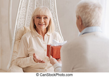 Cheerful delighted woman receiving a present