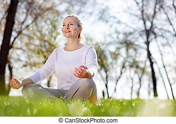 Cheerful delighted woman sitting in the grass