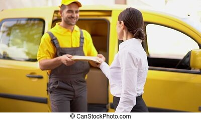 Cheerful delivery man takes a parcel from young woman