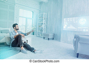 Cheerful designer looking happy while using a remote control at home
