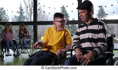 Cheerful disabled teenage boys chatting indoors