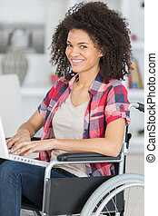cheerful disabled young woman using laptop on wheelchair at home