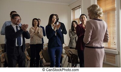 Cheerful diverse co-workers team greeting speaker - Positive...